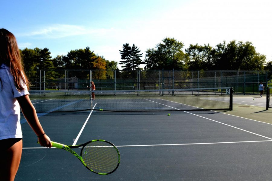 Lucy Lee (Front) and Natalie Yoho (Back) on the Tennis Court Preparing to play versus one another.